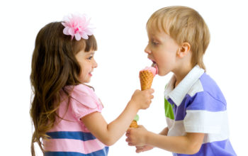 girl shares, gives or feeds boy with her ice cream in studio isolated